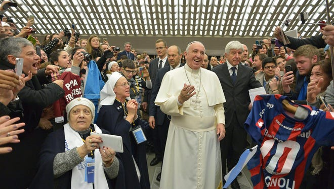 A handout picture provided by the Vatican newspaper L'Osservatore Romano shows Pope Francis among the faithful during his general audience in Vatican City, Vatican, Feb. 4, 2015.