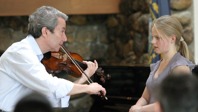 Heifetz International Music Institute Founder and Artistic Director Daniel Heifetz plays violin for a student musician.
