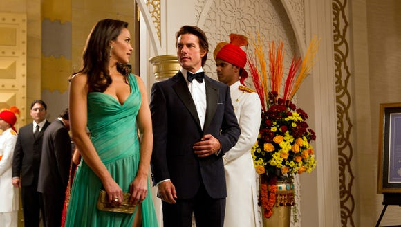 Paula Patton and Tom Cruise, dressed for action in