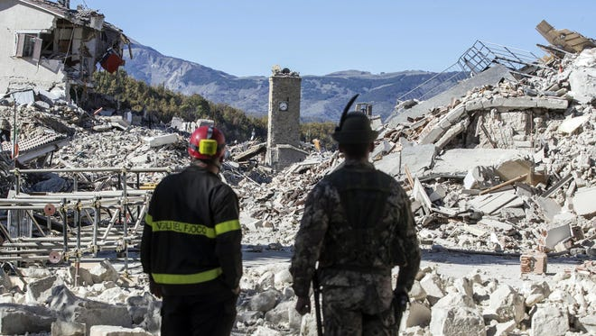 A firefighter, left, and an alpine soldier look at rubble in the hilltop town of Amatrice as an earthquake with a preliminary magnitude of 6.6 struck central Italy, Sunday, Oct. 30, 2016. A powerful earthquake rocked the same area of central and southern Italy hit by quake in August and a pair of aftershocks last week, sending already quake-damaged buildings crumbling after a week of temblors that have left thousands homeless.