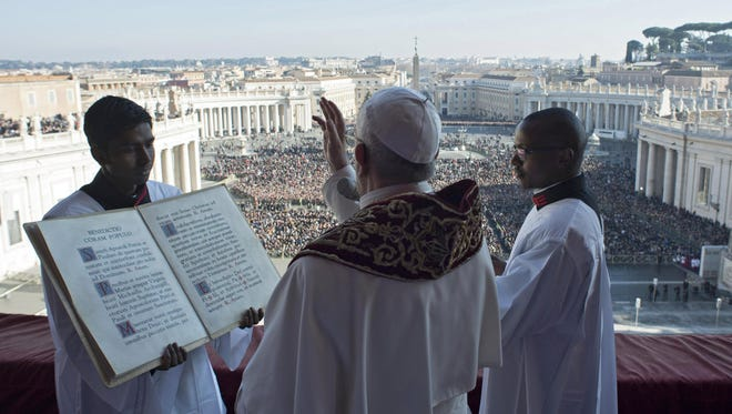 A handout photo made available by Vatican newspaper L'Osservatore Romano shows Pope Francis as he delivers the traditional Urbi et Orbi (to the city and to the world) Christmas Day blessing from the central balcony of St. Peter's Basilica at the Vatican, on Dec. 25, 2017.