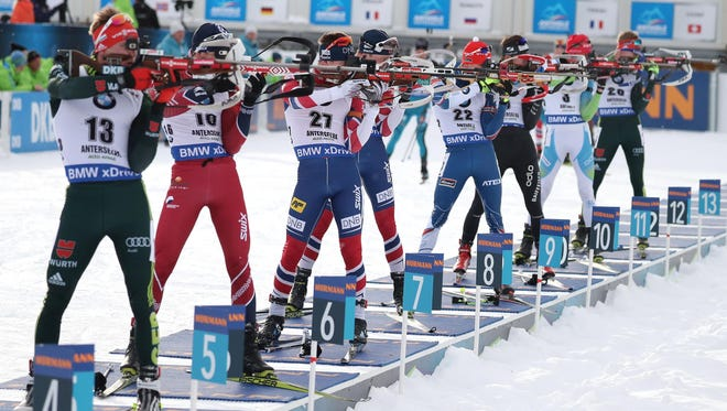 Biathletes in action at the shooting range during the men's 15km Mass Start race at the Biathlon World Cup in January.