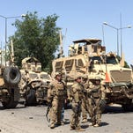 NATO soldies stand guard near the site of a suicide bomb blast that targeted a convoy of foreign troops in Kabul, Afghanistan, 30 June 2015.