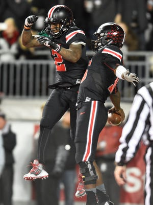 Ohio State quarterback J.T. Barrett celebrates his touchdown run with Dontre Wilson in Saturday night's win over Penn State.
