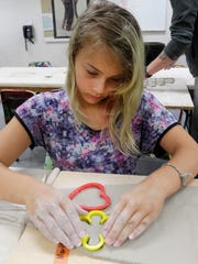 Joslynn Lampe, 12, of Sheboygan works on cutting out shapes for Hope's Hearts chimes on July 27, 2017, at the John Michael Kohler Arts Center in Sheboygan.