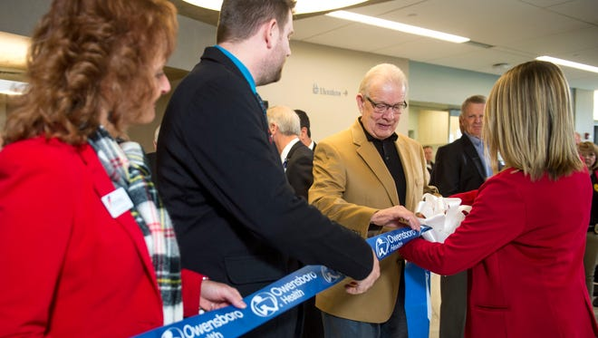 Henderson mayor Steve Austin adjusts the ribbon and bow before the official ribbon cutting of the Owensboro Health Henderson Healthplex in Henderson, Ky., on Thursday, Dec. 14, 2017.
