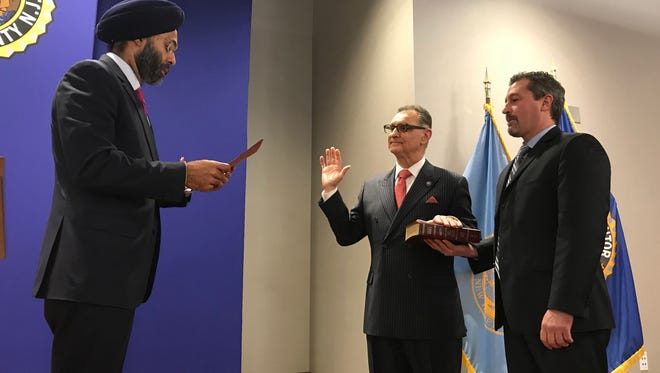 Dennis Calo, center, is sworn in as acting Bergen County prosecutor by his predecessor Gurbir Grewal, at left, while Chief of Detectives Robert Anzilotti holds the Bible Jan. 19, 2018 in Hackensack.