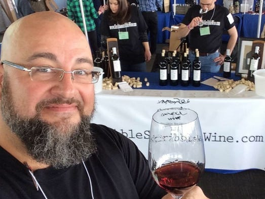 Dean Wilson is shown holding a glass of his wine, Lucille
