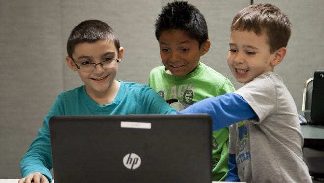 Anthony Dhondt (from left), 9, Cruz Rich, 8, and Ryne Reighley, 6, play their self-coded versions of the video game Minecraft during the Minecraft Mod Design course at Codakid in Scottsdale. The class is designed to teach kids how to code through the video game Minecraft.