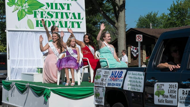 Mint Festival Queens wave to the parade watchers Saturday, August 15, 2015.