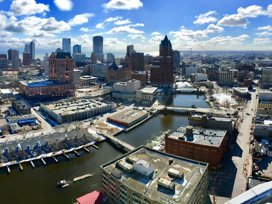 The Milwaukee River flows through downtown Milwaukee with the skyline in the background. On June 18 and 19, overflows of combined sanitary and storm sewers poured 360 million gallons of untreated wastewater into the Milwaukee, Menomonee and Kinnickinnic rivers.