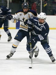 Pittsford's John Avery (5) carries the puck into the