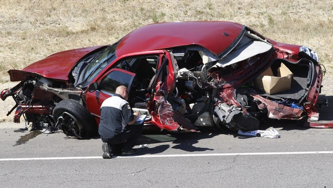 A Law enforcement officer investigates the scene of a two vehicle collision that closed the south bound lanes of Salem Parkway, north of Hyacinth Street NE, on Wednesday, Aug. 27, 2014. No injuries were reported.