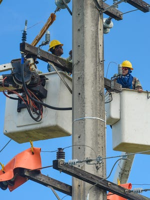 In this Oct. 27, 2016, file photo, Guam Power Authority employees work on power lines and insulators on a utility pole at the Harmon Substation compound.
