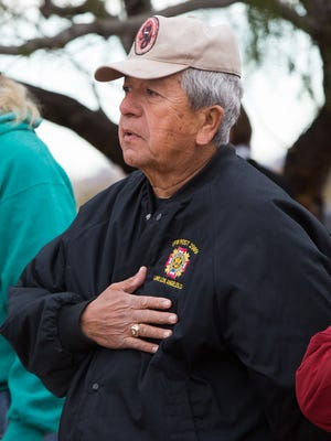 Alfred Lopez, a Navy veteran, holds his hand to his heart as he and a group of around 40 mostly veterans said the pledge of allegiance Wednesday December 7, 2016, during a ceremony to raise the city's garrison flag at Veterans Memorial Park in remembrance of the 1941 attack on Pearl Harbor by the Japanese.