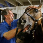Horse dentist Kevin Wirth enjoyed a laugh while inspecting the condition of a saddlebred horse's teeth. Wirth is a horse dentist who treats more than 2,000 horses a year.