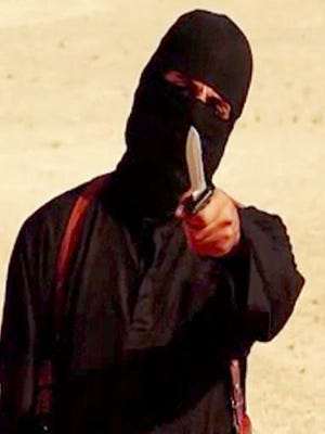 """This file photo shows an image grab taken from a video released by the Islamic State and identified by SITE Intelligence Group on September 2, 2014, purportedly showing British jihadist """"jihadi john"""" holding a knife and gesturing as he speaks to the camera in a desert landscape before beheading 31-year-old U.S. freelance writer Steven Sotloff."""