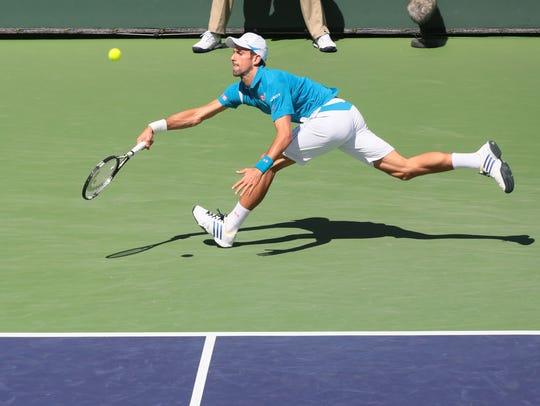 Novak Djokovic, of Serbia, runs down a shot from Rafael