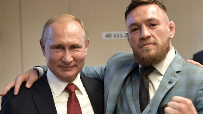 Russian President Vladimir Putin, left, and MMA star Conor McGregor pose for a photo during the World Cup final between France and Croatia.