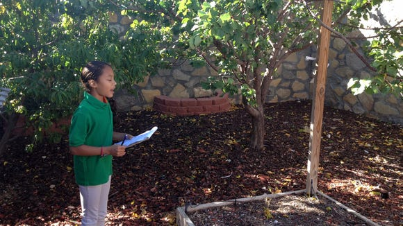 Chester E. Jordan Elementary third-grade student Giselle Kurz explains the school garden.