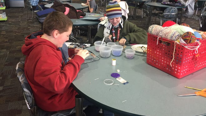 Memorial Middle School students Cadyn Chaput and Alena Schumacher, both 13, work on beading in the school's maker space on Friday, Feb. 10, 2017.