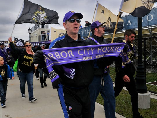 Orlando City Soccer club fans support their team during Sundays game with Eastern Florida State College held at the Melbourne campus soccer field .
