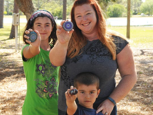 Brevard Rocks is a pay-it-forward group whose Facebook page has over 1,000 members. the idea is for members to paint rocks, and place them around town, for other members to find. In these photos are Jennifer Justiniano and her daughter Aubrey, 11, and son Liam, 5, at Wickham Park, Melbourne, where Liam found a rock as they were placing ones that they had painted and is proudly showing his find in this photo.