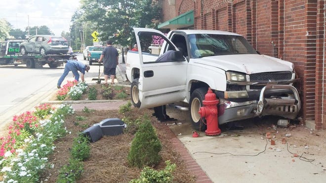 City personnel cleanup after a white truck crashed in to Queensborough National Bank in Wadley last week.