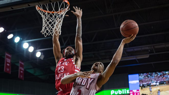 UL's JaKeenan Gant goes up for a block of Troy's Darian Adams during the Cajuns' 81-76 road win over the Trojans on Thursday.