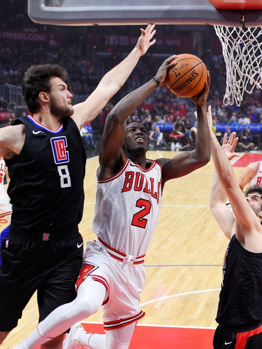 Chicago Bulls guard Jerian Grant, center, shoots as Los Angeles Clippers forward Danilo Gallinari, left, of Italy, and guard Milos Teodosic, of Serbia, defend during the first half of an NBA basketball game, Saturday, Feb. 3, 2018, in Los Angeles. (AP Photo/Mark J. Terrill)