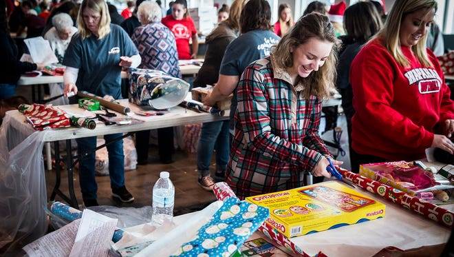 Hundreds of volunteers gather at Toyota of Muncie to wrap and deliver presents during the Secret Families Christmas Charity event Saturday morning. The event purchased and delivered Christmas presents to 352 local families this year.