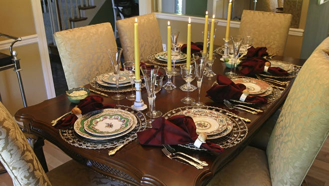 A table set with fine china and candles for a holiday meal.
