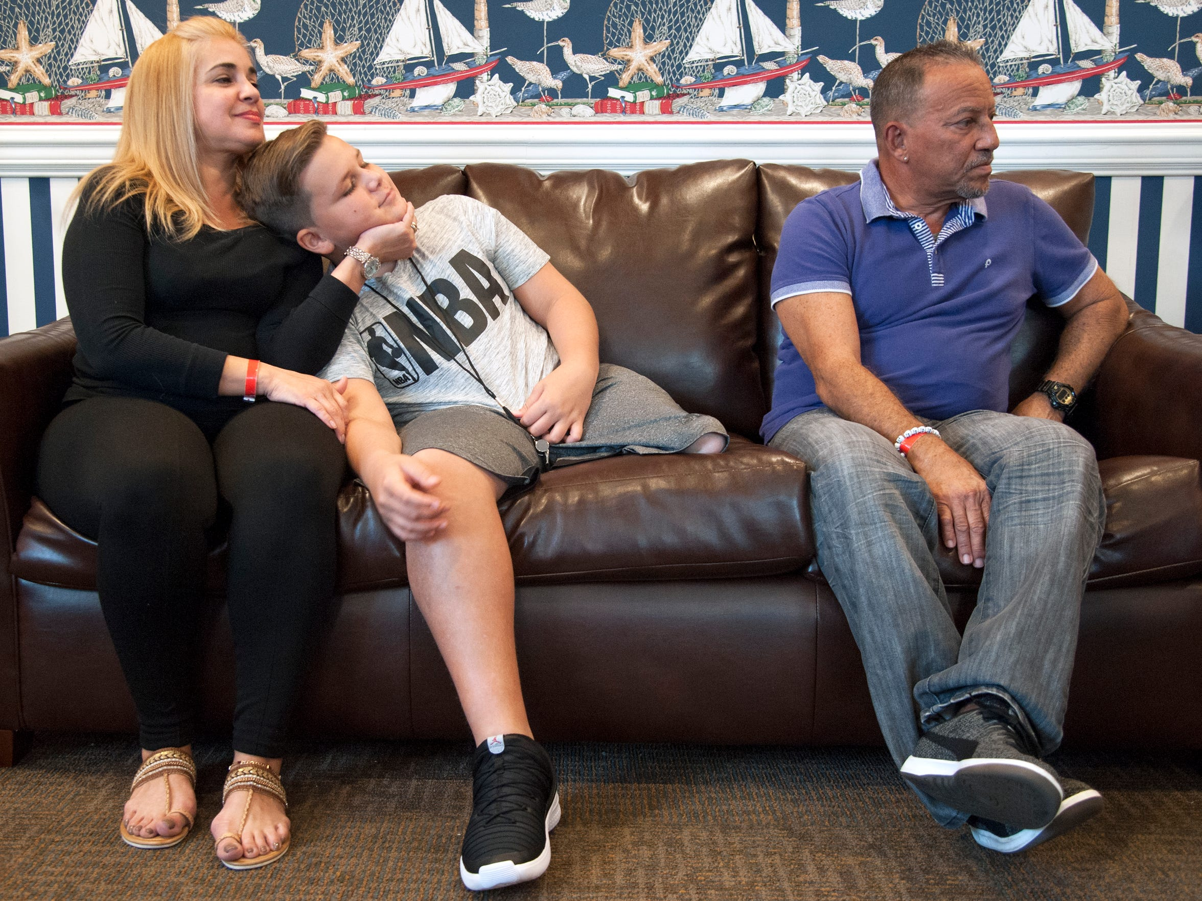 Luis Chiclana, 12 of Puerto Rico, sits with his mother Joana and father Angel in the Ronald McDonald House in Camden.   Luis was born without a tiba and fibia and is staying at the Ronald McDonald House in Camden with his parents while undergoing treatment, and will soon receive a prosthetic leg.  Luis and his parents will be going back to Puerto Rico later this month.  Luis dreams of challenging his idol Michael Jordan to a game.