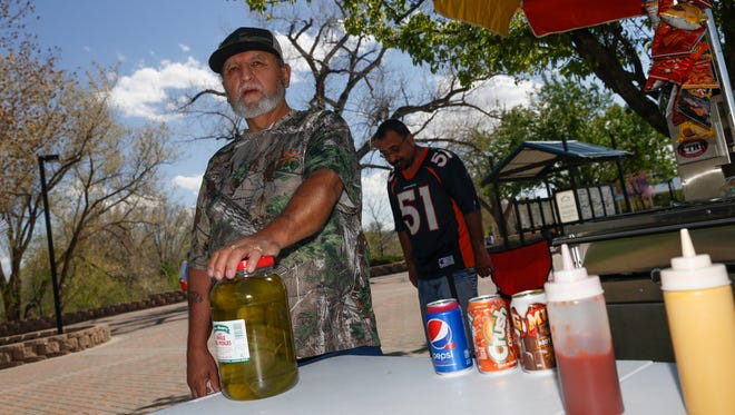 Hot Dogs Galore owner Daniel Martinez, left, and his son Julian Martinez wait for customers on April 24, 2018 at Berg Park in Farmington.