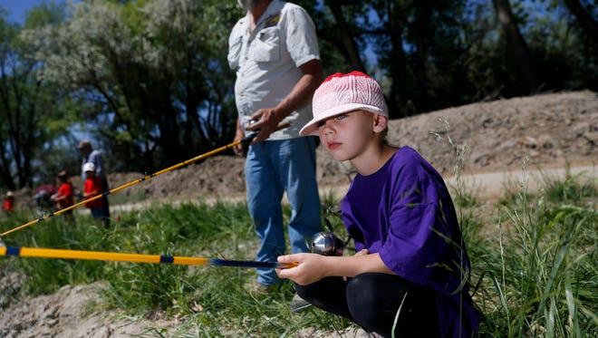 Student Alivia Cordell fishes with volunteer Dar Gunnink Friday at Riverside Pond in Aztec.