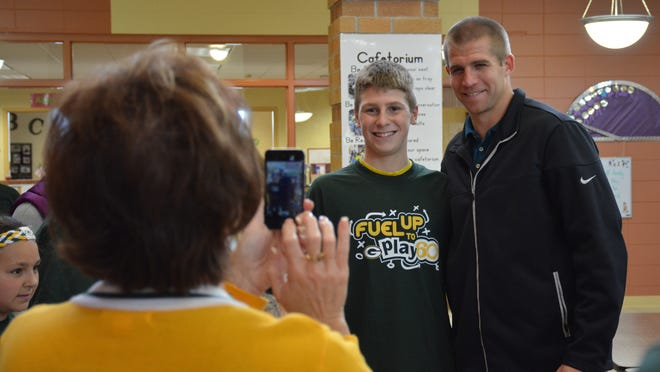 Nick Baumgartner stands for a photo with Jordy Nelson while Principal Karen Treml takes a shot with her phone.