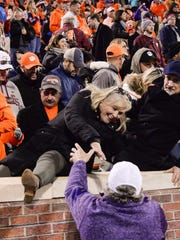 Clemson fans climb over the wall to get on the field after the game in Memorial Stadium at Clemson on Saturday.