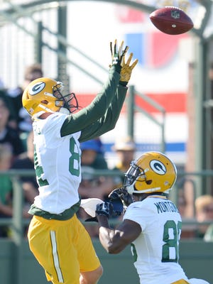 Receiver Jared Abbrederis (84) jumps during a passing drill with Ty Montgomery (88) at Green Bay Packers Training Camp at Ray Nitschke Field July 30, 2015.