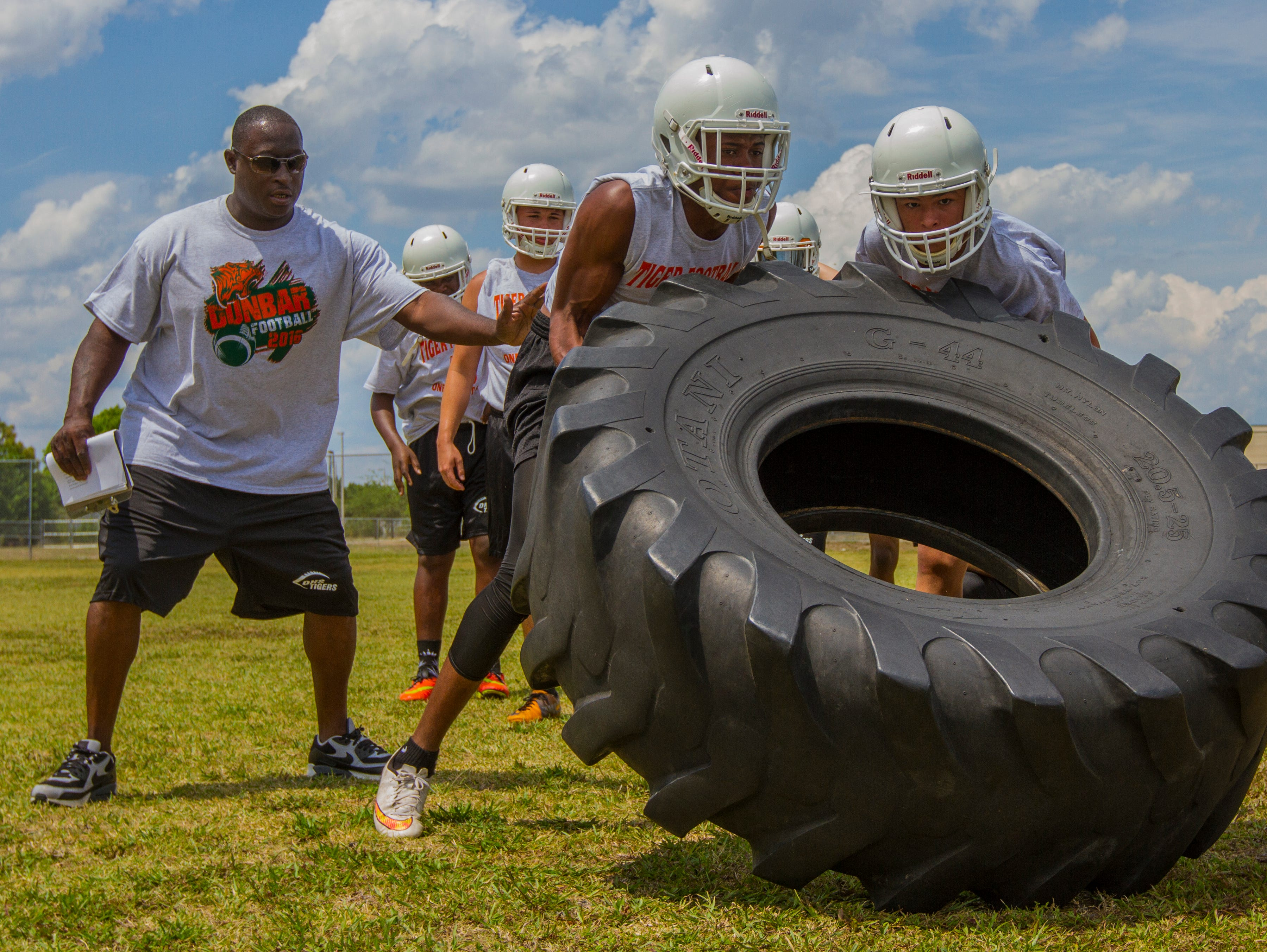 Dunbar High School's interim football coach Sammy Brown works on strength and conditioning drills with his players during an after school practice Monday (4/25/16) in Fort Myers.