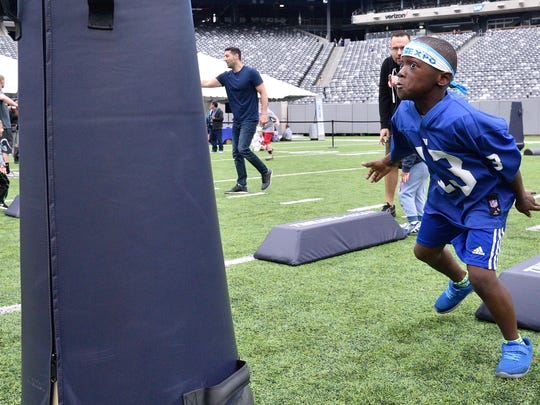 Jaden Francis,9, of Plainfield rushes toward a tackling dummy at the NBC 4 New York and Telemundo 47 Health & Fitness Expo at Metlife Stadium in East Rutherford on Saturday, June 23, 2018.