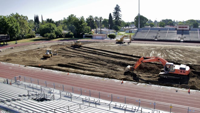 A construction crew works to improve the playing field at Tulare's Bob Mathias Stadium on Wednesday, June 28, 2017.