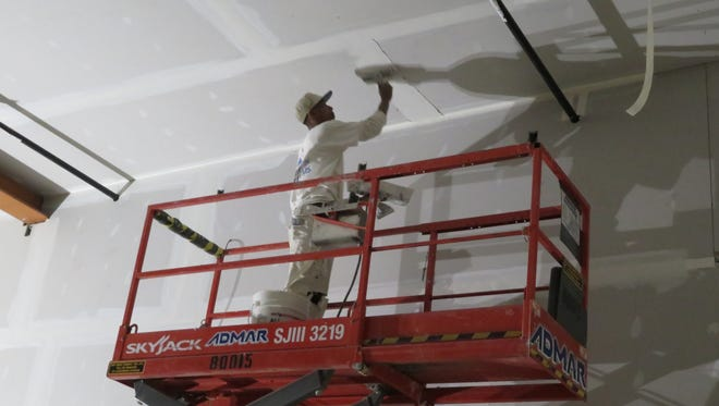 A worker seals the seams in ceiling sheet rock at the downtown Binghamton space that will be converted into Dos Rios Cantina, a new Mexican restaurant.