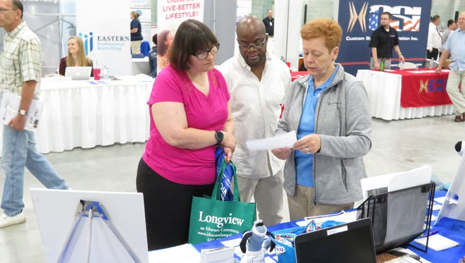 Debra Reardon, marketplace facilitated enrolled with United Healthcare Community Plan, speaks to two prospective candidates at the Greater Binghamton Chamber of Commerce Job Fair at the SUNY Broome Ice Arena on Friday, June 15, 2018.