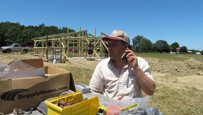 Jeb Puryear, president of the GrassRoots organization, takes a phone call while he works at the festival site.
