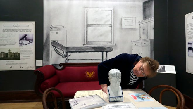 Carol Brueggemann of Appleton checks out a Phrenology bust as part of an examination room display Thursday at the History Museum at the Castle. The examination room display is part of the new Outagamie County Asylum for the Chronic Insane exhibit.