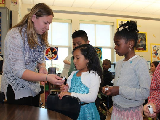 Health Quest registered dietitian Theresa Zangerle-McArtin, left, gives pedometers to some Krieger Elementary third-graders.