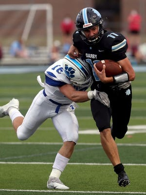 Hilliard Darby's Blake Horvath tries to shake off Hilliard Davidson's Kyle Pepera during the opener Aug. 27.