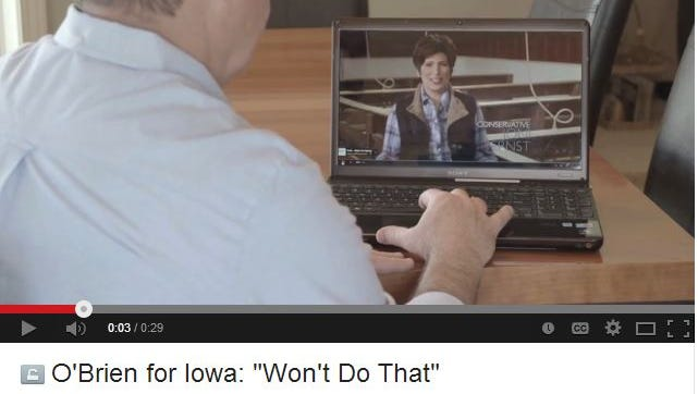 """This screenshot shows Iowa congressional candidate Dave O'Brien, a Democrat, watching Republican U.S. Senate candidate Joni Ernst's """"Squeal"""" ad in his new """"Won't Do That"""" TV ad."""