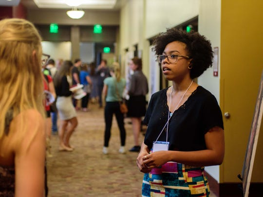 Menika Lue discusses her research with fellow students and faculty.