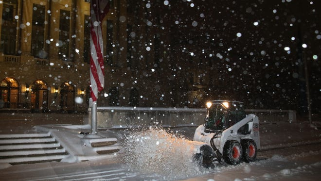Workers remove snow in front of the Department of Agriculture on March 17 in Washington, D.C.